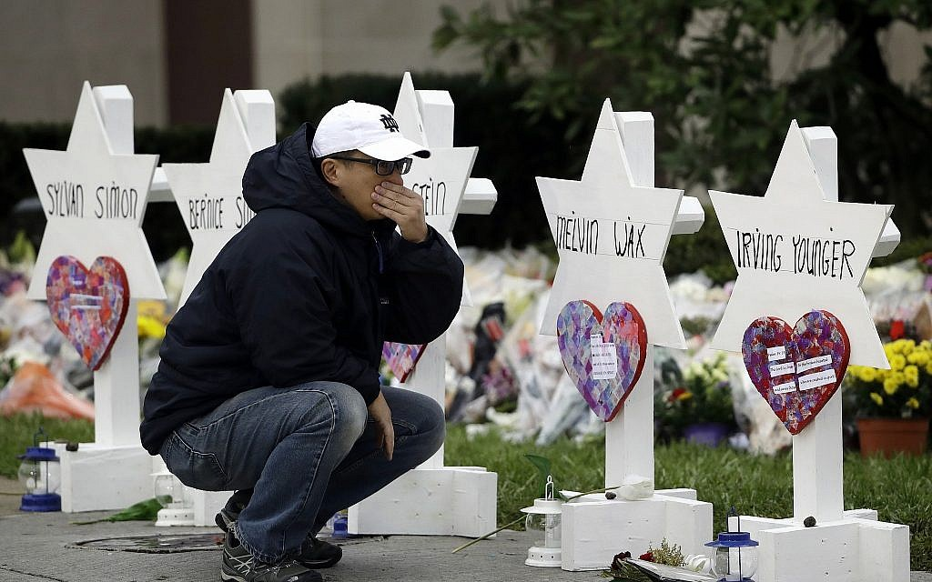 In this October 29, 2018, file photo, a person pauses in front of Stars of David with the names of those killed in a deadly shooting at the Tree of Life Synagogue, in Pittsburgh. (AP Photo/Matt Rourke)