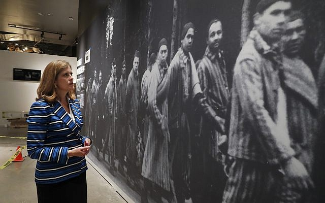 In this July 29, 2019, photo, Dallas Holocaust and Human Rights Museum President and CEO, Mary Pat Higgins, pauses as she gives a tour of the museum in Dallas, to look at a wall size image of Jews marching. When Dallas' Holocaust museum reopens in a few weeks it will not only be in a new building five times the size of its previous location, but will take visitors on a journey that also includes modern-day genocides and the evolution of human and civil rights in the U.S. (AP Photo/Tony Gutierrez)