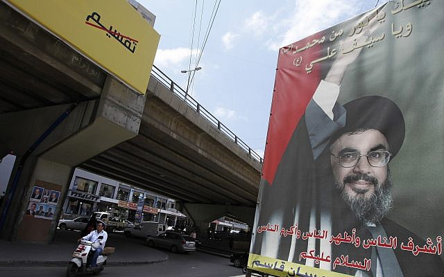 In this photo taken Monday, May 11, 2009, a motorcyclist drives past a poster of Hezbollah leader Sheik Hassan Nasrallah in Beirut's southern suburb of Dahiyeh, Lebanon. (AP/Bilal Hussein)