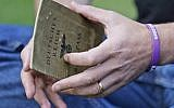 Illustrative photo of a man holding a Nazi-era German passport that belonged to his grandparent, October 5, 2016. (Frank Augstein/AP)