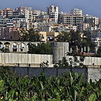 In this May 5, 2017 photo, a general view of the concrete wall surrounding the Ein el-Hilweh Palestinian refugee camp near the southern port city of Sidon, Lebanon (AP Photo/Bilal Hussein)