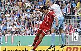 Illustrative: Bayern's Mats Hummels, left, challenges for the ball against Chemnitz' Tom Scheffel, right, during the German soccer cup match between Chemnitzer FC and and FC Bayern Munich in Chemnitz, eastern Germany on August 12, 2017. (AP/Jens Meyer)