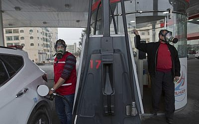 Two Palestinian gas station workers wear teargas masks while supplying vehicles with gasoline during clashes following protests against US President Donald Trump's decision to recognize Jerusalem as the capital of Israel, in the West Bank city of Ramallah, Thursday, Dec. 21, 2017. (AP/Nasser Nasser)