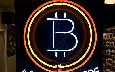FILE - In this Feb. 7, 2018 file photo, a neon sign hanging in the window of Healthy Harvest Indoor Gardening in Hillsboro, Oregon, shows that the business accepts bitcoin as payment. (AP Photo/Gillian Flaccus, File)