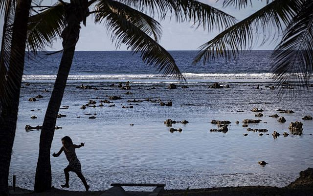 A child plays near the beach in Nauru during the Pacific Islands Forum on the tiny Pacific nation of Nauru Monday, Sept. 3, 2018. (Jason Oxenham/Pool Photo via AP)