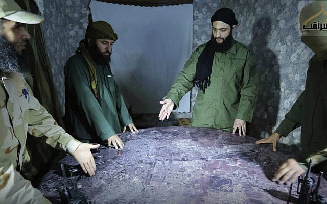Illustrative: This undated file photo released in 2016, shows Abu Mohammed al-Golani of the Levant Liberation Committee and the leader of Syria's al-Qaida affiliate, second right, discussing battlefield details with field commanders over a map, in Aleppo, Syria.  (Militant UGC via AP, File)