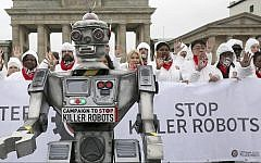 People take part in a 'Stop killer robots' campaign at Brandenburg gate in Berlin, Germany, Thursday, March 21, 2019. (Wolfgang Kumm/dpa via AP)