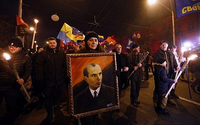 In this January 1, 2019, file photo, activists of various nationalist parties carry torches, Ukrainian national flags and a portrait of Stepan Bandera during a rally in Kyiv, Ukraine. (AP Photo/Efrem Lukatsky, File)