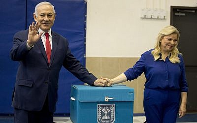 Prime Minister Benjamin Netanyahu, left, waves with his wife Sara after voting during parliamentary elections in Jerusalem on April 9, 2019. (AP/Ariel Schalit, Pool)