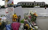 Signs of support and flowers adorn a post in front of the Chabad of Poway synagogue, April 29, 2019, in Poway, California. (AP/Gregory Bull)