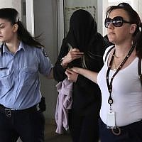 Police officers escort a 19-year-old British woman, center, from the Famagusta court in town of Paralimni, Cyprus, Monday, July 29, 2019. (AP/Petros Karadjias)