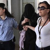 Police officers escort a 19-year-old British woman, center, from the Famagusta court in town of Paralimni, Cyprus, July 29, 2019. (AP/Petros Karadjias)