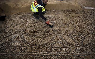 In this July 16, 2019 photo, Palestinians work on a preservation of a Byzantine period mosiac near Jebaliya refugee camp, northern Gaza Strip. (AP Photo/Khalil Hamra)