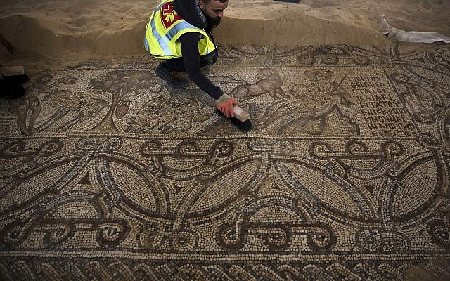 In this July 16, 2019 photo, Palestinians work on a preservation of a Byzantine period mosiac near Jebaliya refugee camp, northern Gaza Strip. (AP Photo/Khalil Hamra)