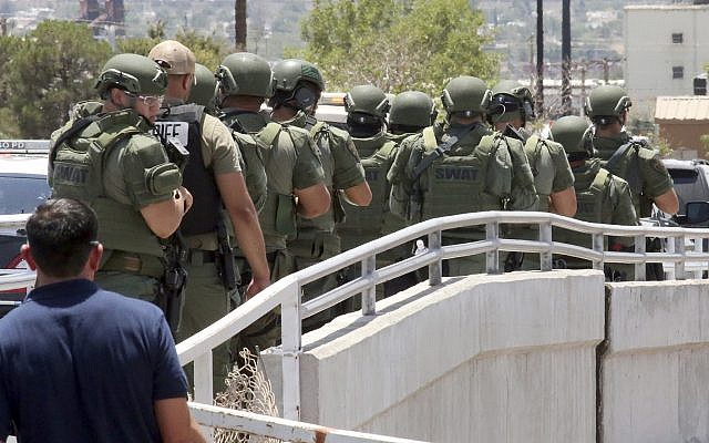 Law enforcement officers make their way along a walkway to the scene of a shooting at a shopping mall in El Paso, Texas, on Aug. 3, 2019 (AP Photo/Rudy Gutierrez)
