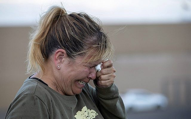 Edie Hallberg cries while speaking to police outside a Walmart store where a shooting occurred earlier in the day as she looks for her missing mother Angie Englisbee, who was in the store during the attack in El Paso, Texas, Aug. 3, 2019 (AP Photo/Andres Leighton)