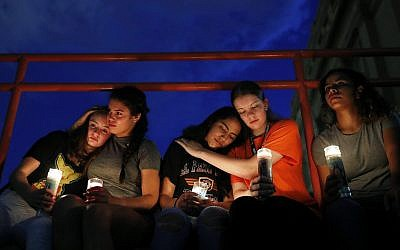 From left, Melody Stout, Hannah Payan, Aaliyah Alba, Sherie Gramlich and Laura Barrios comfort each other during a vigil for victims of the shooting August  3, 2019, in El Paso, Texas. (AP Photo/John Locher)