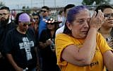 Cathe Hill wipes tears from her eyes during a vigil for victims of Saturday's mass shooting at a shopping complex, August 4, 2019, in El Paso, Texas. (AP Photo/John Locher)