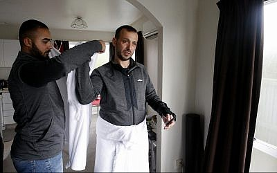In this July 31, 2019, photo, Temel Atacocugu, who was shot nine times during the Christchurch mosque attacks, tries on the clothes he will wear during the Hajj pilgrimage, in Christchurch, New Zealand. (AP Photo/Nick Perry)
