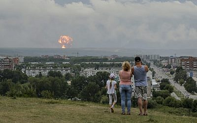 A family watches explosions at a military ammunition depot near the city of Achinsk, Russia on  Aug. 5, 2019. (AP Photo/Dmitry Dub)