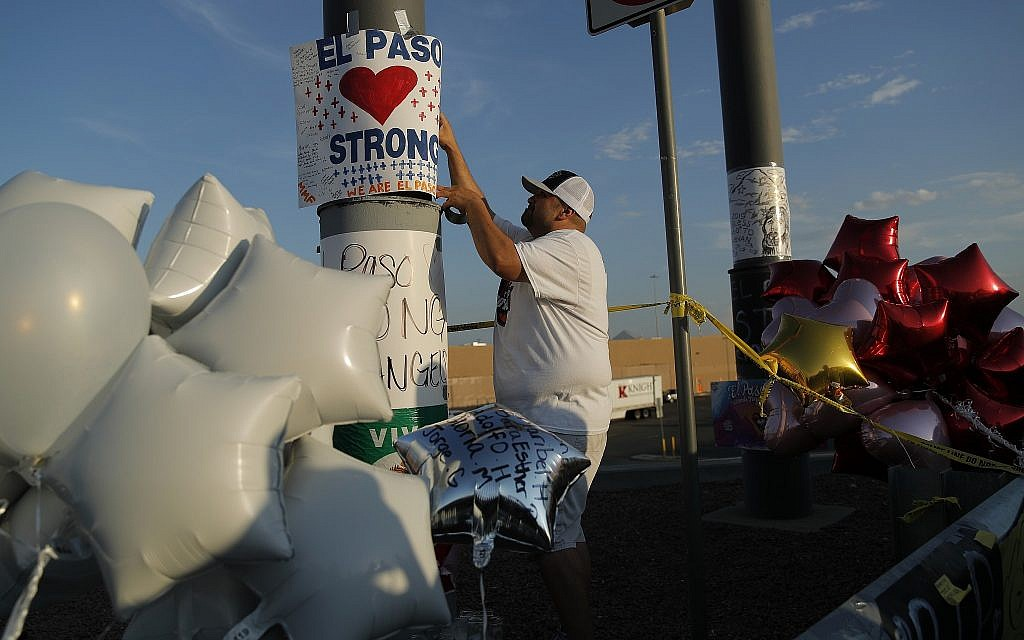 "A man hangs up an ""El Paso Strong"" sign at a makeshift memorial at the scene of a mass shooting at a shopping complex, August 6, 2019, in El Paso, Texas. (AP Photo/John Locher)"
