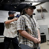 In this July 21, 2019 photo, Brett Faulkner, left, fires blanks out of an assault rifle as he and Julia Gant, right, participate in a hostage-taking scenario during a security training session at Fellowship of the Parks campus in Haslet, Texas. (AP/Tony Gutierrez)