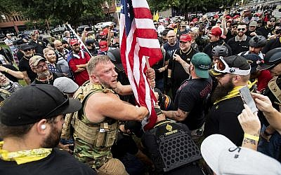 Joseph Oakman and fellow Proud Boys plant a flag in Tom McCall Waterfront Park during a rally in Portland, Oregon, on August 17, 2019. (AP Photo/Noah Berger)