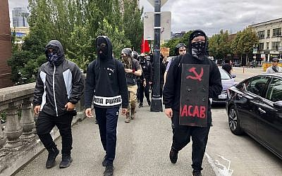 Anti-fascist counter-demonstrators cross the Burnside Bridge across the Willamette River from the west side of the city to the east side in search of the far-right group, the Proud Boys, in Portland, Ore., Saturday, Aug. 17, 2019. (AP Photo/Gillian Flaccus)