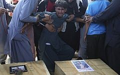 A relative wails near the coffins of victims of the Dubai City wedding hall bombing during a mass funeral in Kabul, Afghanistan, Sunday, Aug.18, 2019. (AP Photo/Rafiq Maqbool)