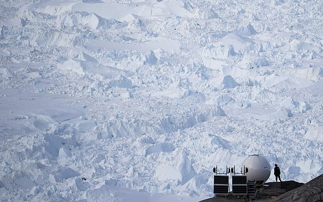 In this Aug. 16, 2019, photo, a woman stands next to an antenna at an NYU base camp at the Helheim glacier in Greenland.  (AP Photo/Felipe Dana)