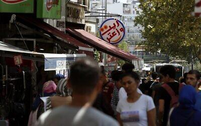 In this photo taken on August 20, 2019, people walk past Syrian restaurants in the Istanbul neighborhood of Aksaray in Turkey. (AP Photo/Lefteris Pitarakis)