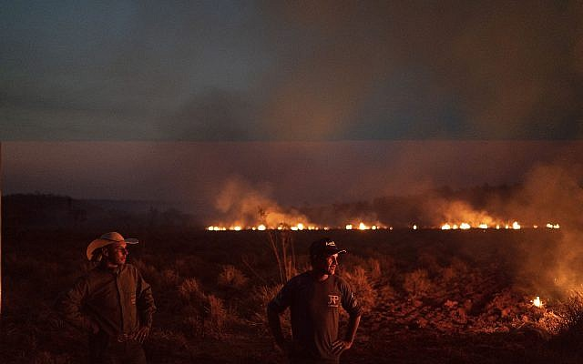 Neri dos Santos Silva, center, watches an encroaching fire threat after digging trenches to keep the flames from spreading to the farm he works on, in the Nova Santa Helena municipality, in the state of Mato Grosso, Brazil, Friday, Aug. 23, 2019. Under increasing international pressure to contain fires sweeping parts of the Amazon, Brazilian President Jair Bolsonaro on Friday authorized use of the military to battle the massive blazes. (AP Photo/Leo Correa)