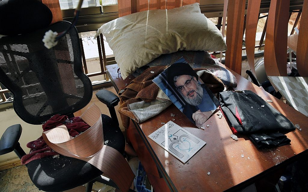 A poster of Hezbollah leader Sayyed Hassan Nasrallah is seen amid other damage inside the media office in a stronghold of the Lebanese Hezbollah group in a southern suburb of Beirut, Lebanon, Sunday, Aug. 25, 2019. (AP/Bilal Hussein)
