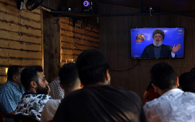 People listen to a speech by Hezbollah leader Sayyed Hassan Nasrallah being broadcast on Hezbollah's al-Manar TV channel, in a southern suburb of Beirut, Lebanon, Sunday Aug. 25, 2019. (AP/Bilal Hussein)