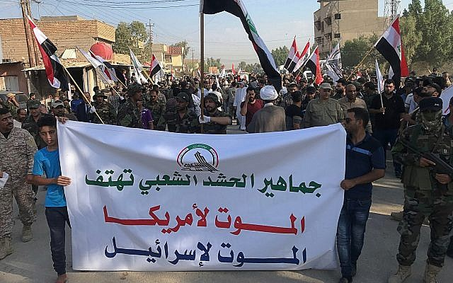 """Mourners hold a banner with Arabic that reads, """"Masses of the Popular Mobilization Forces chant death to America, death to Israel"""" during the funeral procession of Abu Ali al-Dabi, a fighter of the Popular Mobilization Forces, who was killed in a drone attack, in Baghdad, Iraq, August 26, 2019.  (AP Photo/Ali Abdul Hassan)"""