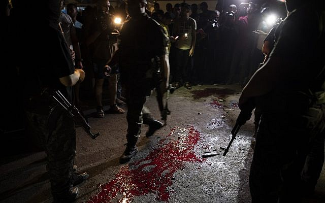 Palestinian Hamas masked gunmen stand guard around blood on the ground following an explosion targeted a Hamas police checkpoint in Gaza City, Tuesday, Aug. 27, 2019. (AP Photo/Khalil Hamra)