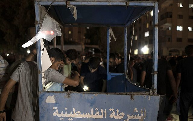 Palestinians check a damaged police booth following an explosion targeted a Hamas police checkpoint in Gaza City, Tuesday, Aug. 27, 2019. (AP Photo/Khalil Hamra)