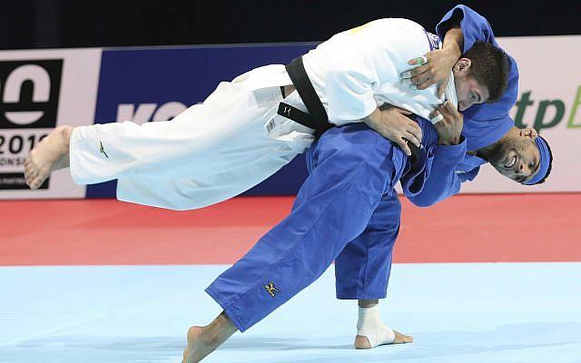 Judoka Luka Maisuradze of Georgia, top, competes against Saeid Mollaei of Iran during a men's under-81 kilogram bronze medal match at the World Judo Championships in Tokyo, August 28, 2019. (AP Photo/Koji Sasahara)