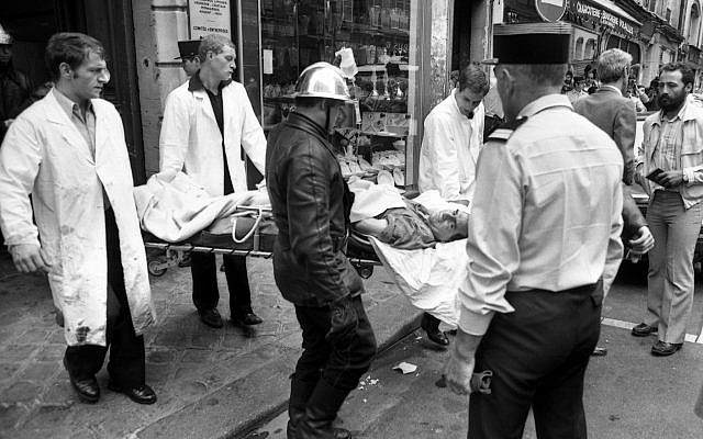 A police officer looks at an injured man being carried away on a stretcher from the scene of a terror attack at Jewish restaurant and deli Jo Goldenberg in Paris, France, on Aug. 9, 1982. The attack left six dead and many injured. (AP Photo/ Lionel Cironneau)