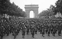 US soldiers of Pennsylvania's 28th Infantry Division march along the Champs Elysees, the Arc de Triomphe in the background, on Aug. 29, 1944, four days after the liberation of Paris, France (AP Photo/Peter J. Carroll)