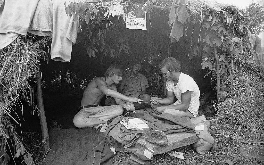 This August 17, 1969 black-and-white file photo shows music fans seeking shelter is a grass hut at the Woodstock Music and Art Festival in Bethel, New York where the sign above reads 'Have a Marijuana.' (AP Photo, File)