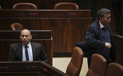 Amir Peretz (R) walks by Naftali Bennett during a Knesset plenum session on January 21, 2015. (Hadas Parush/Flash90)