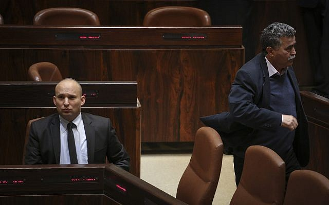 Amir Peretz (R) walks by Naftali Bennett during a Knesset plenum session on January 21, 2015. (Hadas Parush/Flash90)