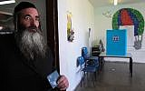 Illustrative: An ultra-Orthodox man casts his vote at a polling station during general elections on March 17, 2015. (Nati Shohat/FLASH90)
