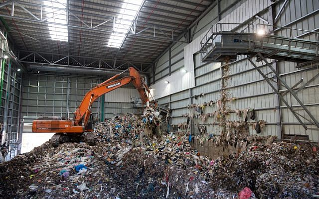 A bulldozer lifts waste at the Greenet recycling plant in Atarot industrial zone, north of Jerusalem on June 16, 2015. (Yonatan Sindel/Flash90)