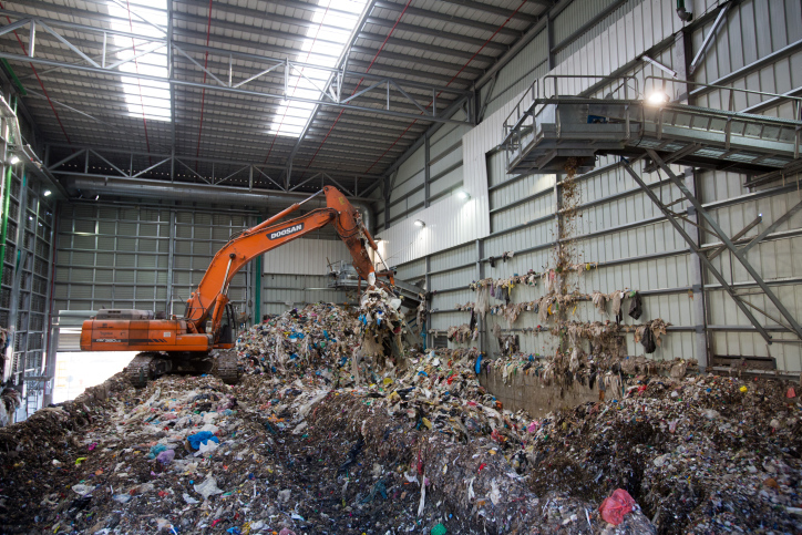 A bulldozer lifts waste at the Greenet recycling plant in the Atarot industrial zone, north of Jerusalem, June 16, 2015. (Yonatan Sindel/Flash90)