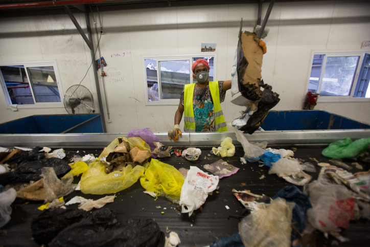 Workers sorting garbage by at the Greenet recycling plant in Atarot industrial zone, north of Jerusalem on June 16, 2015. Automated sorting allows the process to go four times as fast. (Yonatan Sindel/Flash90)
