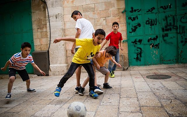 Illustrative: Young Arab boys play football in the alleyways of the Muslim quarters in Jerusalem's Old City on April 8, 2016. (Corinna Kern/Flash90)
