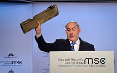 Prime Minister Benjamin Netanyahu shows a part of an Iranian drone as he speaks at the Munich Security Conference in Munich, Germany, on February 18, 2018. (Amos Ben Gershom/GPO)