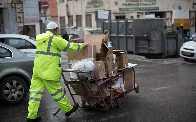 A garbage worker takes cardboard boxes to recycling at the Mahane Yehuda Market in Jerusalem, on February 27, 2019. (Hadas Parush/Flash90)